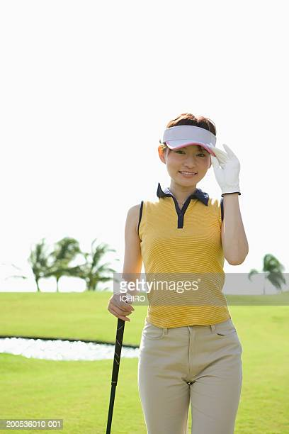young woman adjusting sun visor on golf course, smiling, portrait - adjusting stock pictures, royalty-free photos & images
