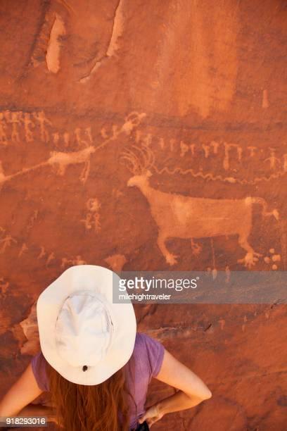Young woman admires Comb Ridge Procession Panel Utah rock art