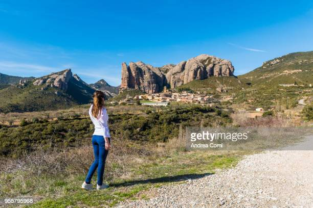 a young woman admires the view of aguero village with mallos de aguero in the background. aguero, huesca, aragon, spain - iberian stock photos and pictures