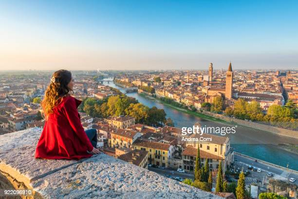 a young woman admires the view of verona old town from castel san pietro - international landmark stock pictures, royalty-free photos & images