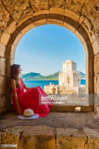 young woman admiring methoni fortress from an ancient window, messenia, peloponnese, greece - greece stock pictures, royalty-free photos & images