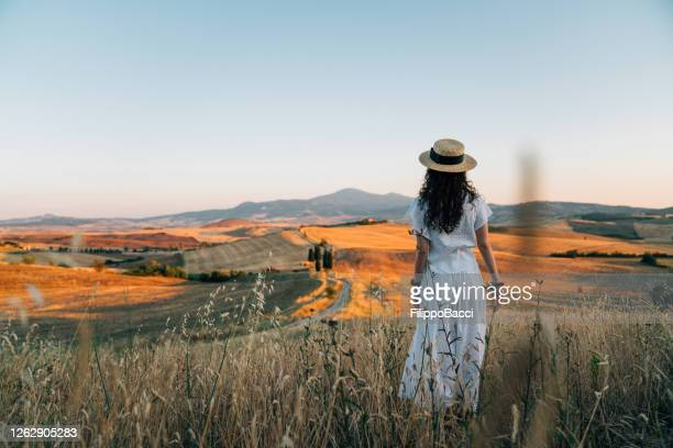 young woman admiring sunset in a wheat field in tuscany - val d'orcia stock pictures, royalty-free photos & images