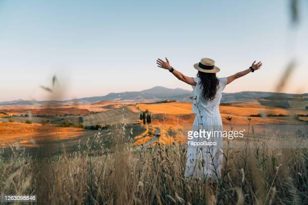 jonge vrouw die zonsondergang op een tarwegebied in toscane met open wapens bewondert - witte jurk stockfoto's en -beelden