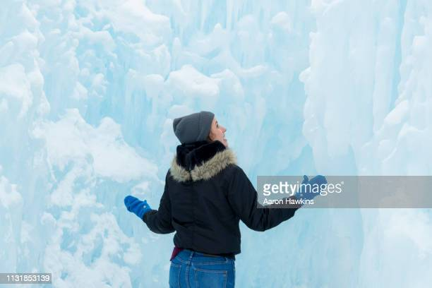 young woman admiring the beauty of an passageway carved into an icy structure - igloo stock pictures, royalty-free photos & images
