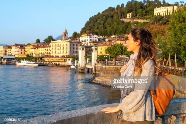 a young woman admiring the sunset from bellagio village - コモ ストックフォトと画像