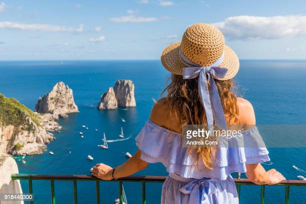 A young woman admiring the view of Capri island. Capri, Naples, Campania, Italy