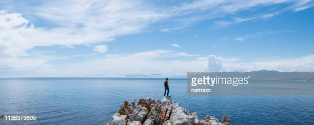 young woman admiring the view over the sea - panoramic stock pictures, royalty-free photos & images