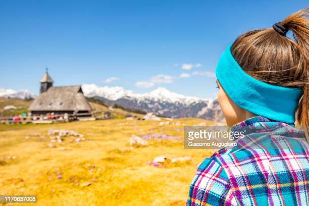 young woman admiring the wooden church of our lady of the snows in velika planina, stahovica, upper carniola region, slovenia, europe - eden pastora fotografías e imágenes de stock