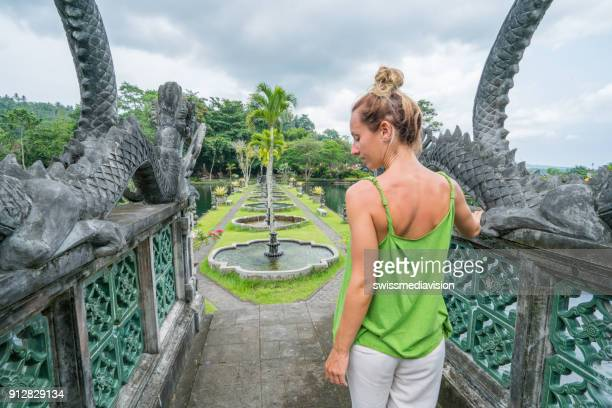 Young woman admiring Tirta Gangga temple, Bali, Indonesia