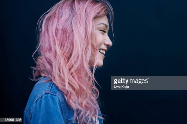 young woman against black background - pink hair stock pictures, royalty-free photos & images