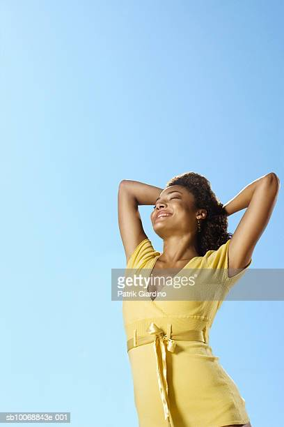 Young woman against sky, smiling