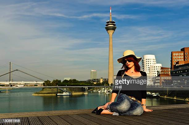 Young woman against the backdrop of Media Harbour in the evening sun, Duesseldorf, North Rhine-Westphalia, Germany, Europe
