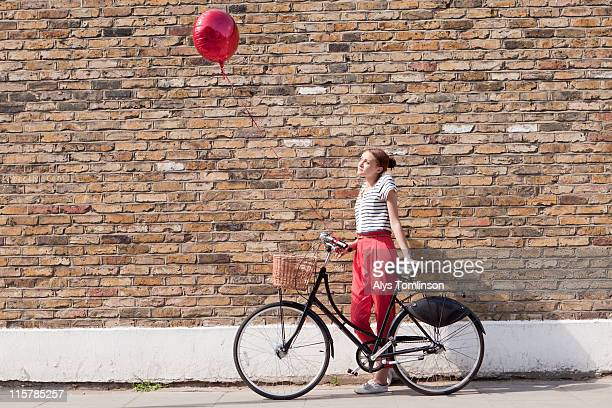 young woman against wall with bike and balloon - basket stock pictures, royalty-free photos & images