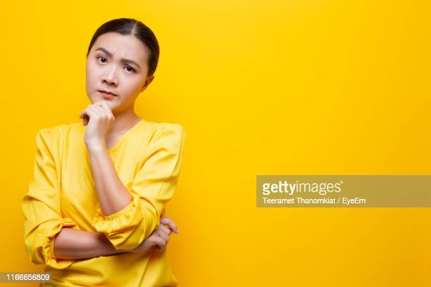 young woman against yellow background - 眉を上げる ストックフォトと画像
