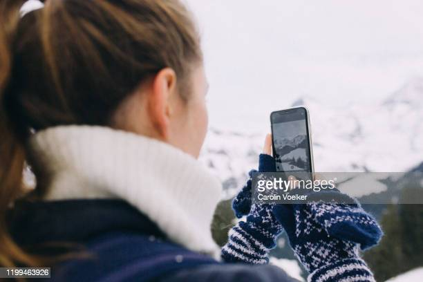 young woman aged 20-24 taking pictures with mobile phone of snowcapped mountain range of eiger, mönch, jungfrau during winter in lauterbrunnen, switzerland - bern stock pictures, royalty-free photos & images