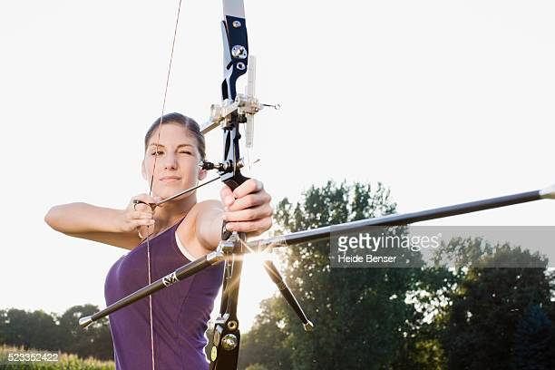 Young woman aiming a bow and arrow