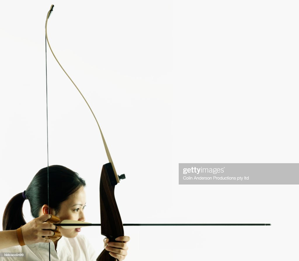 Young woman aiming a crossbow : Stock Photo