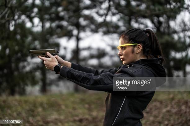 giovane donna che punta e pratica tiro da pistola al poligono di tiro - armi foto e immagini stock
