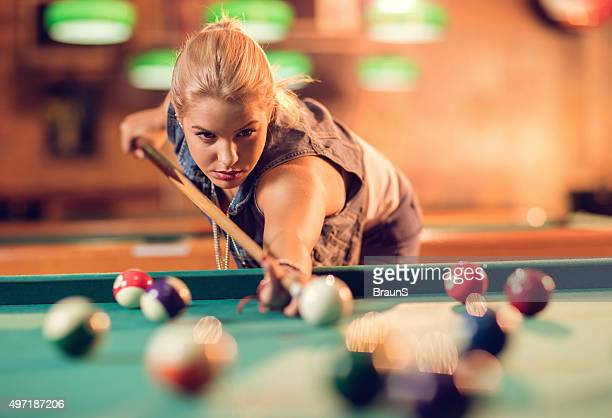 Young woman aiming at pool ball while playing snooker.