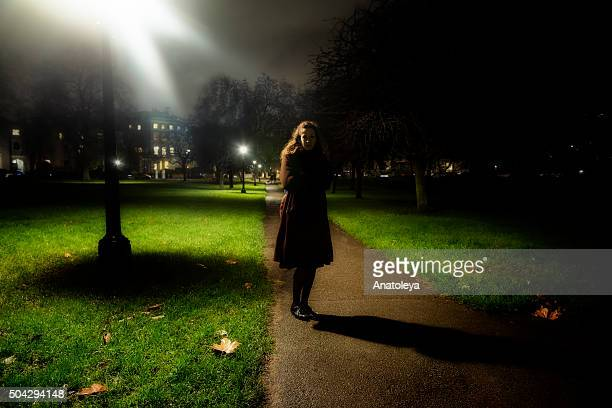 Young woman alone in a park at night