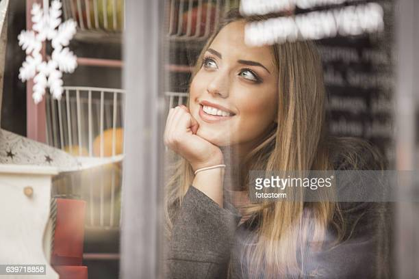 Young woman alone watching on the street trough the window