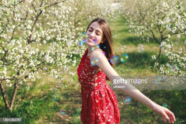 ung kvinna bland blommande träd - flerfärgad klänning bildbanksfoton och bilder