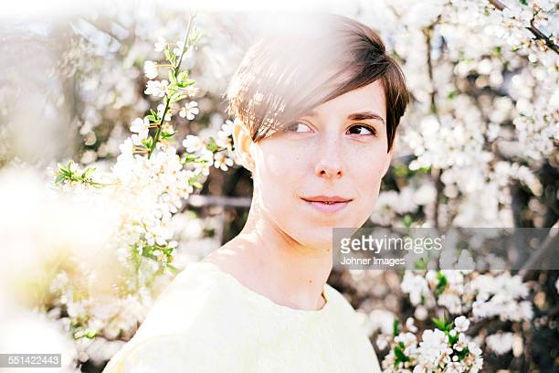 Young woman among blossoming trees