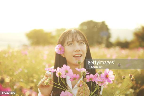 Young woman among cosmos flowers, portrait