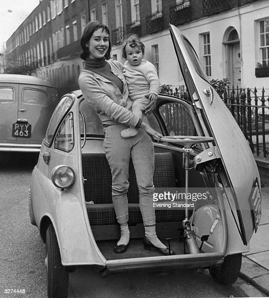 A young woman and a child getting out of an Isetta 'Bubble' car