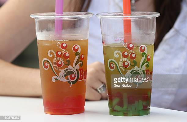 A young woman and a friend enjoy bubble tea outside a bubble tea cafe on August 22 2012 in Berlin Germany Bubble tea which fuses Asian tea with milk...