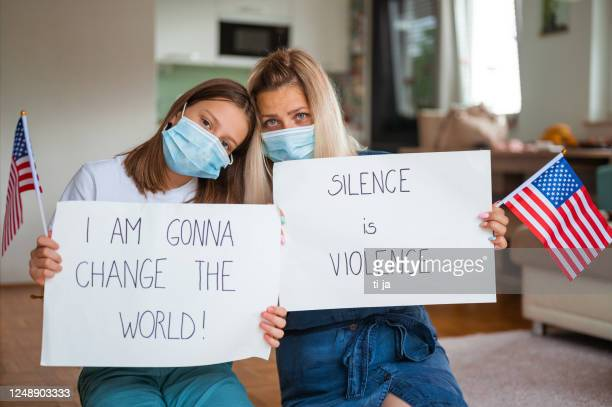 young woman and a little girl, both with face masks holding a poster with anti-racist messages - black civil rights stock pictures, royalty-free photos & images
