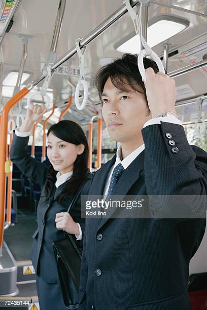 A young woman and a mid adult man standing in a bus