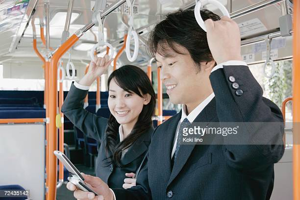 A young woman and a mid adult man talking in a bus