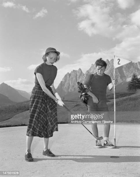 A young woman and a teen age boy playing golf in Cortina 1951