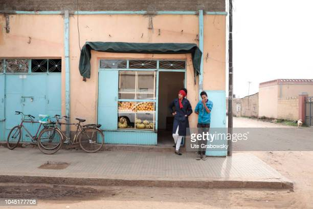 A young woman and a teenager are standing in front of a grocery in the capital of Eritrea on August 24 2018 in Asmara Eritrea