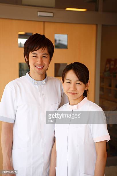 A Young Woman and A Young Man Smiling, Serving Elderly Care, Looking at Camera