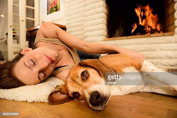 Jeune femme et chien beagle sur le sol à côté de la cheminée