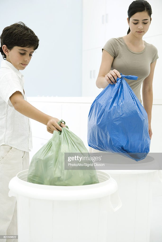 Young woman and boy placing garbage bags in separate garbage cans : Stock Photo