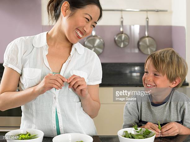 Young woman and boy preparing peas
