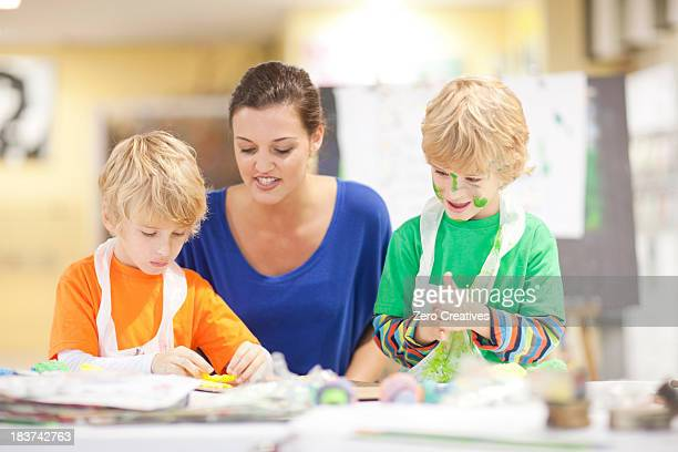 Young woman and boys in art class