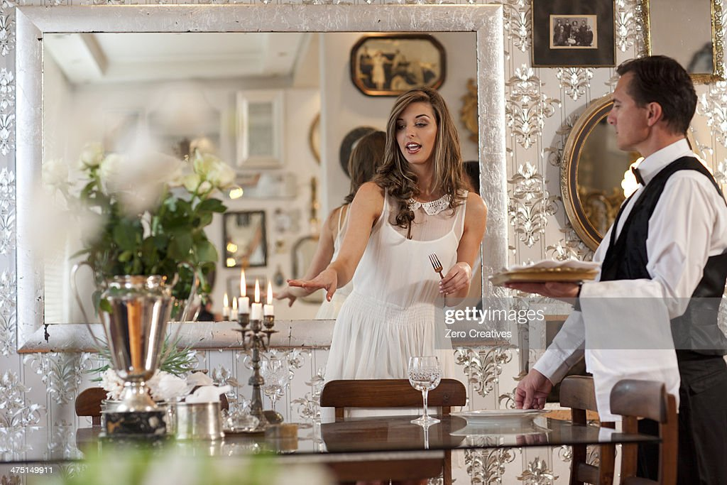 Young woman and butler in dining room : Stock Photo