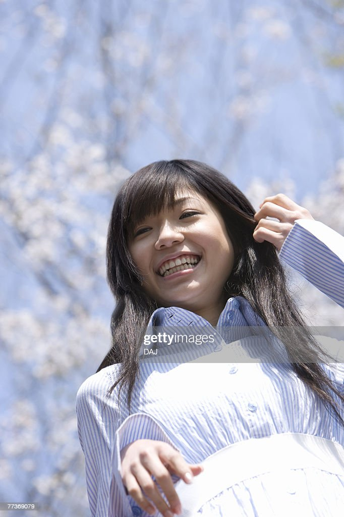Young Woman and Cherry Blossom in the Background, Low Angle View : Photo