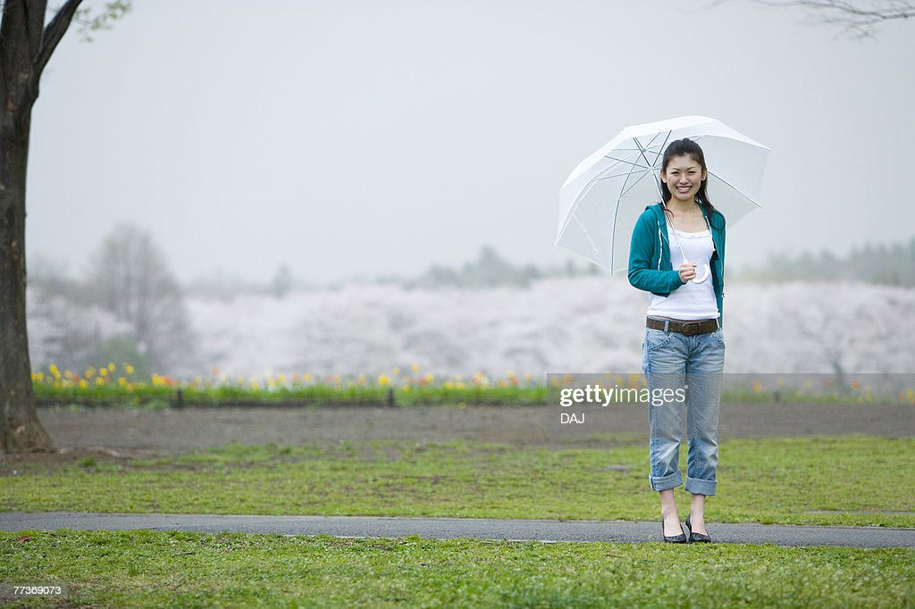 Young Woman and Cherry Blossoms in the Background, Front View : Photo