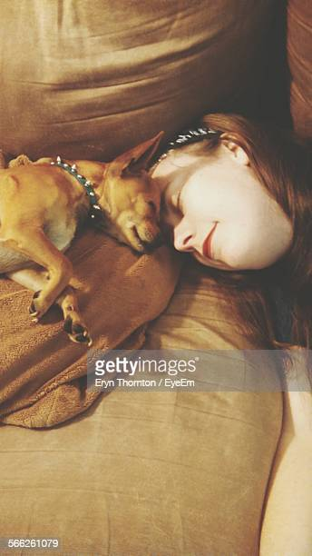 Young Woman And Chihuahua Sleeping On Sofa