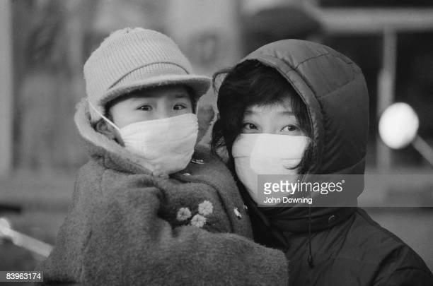 A young woman and child wearing smog masks China February 1985