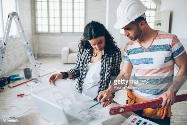 young woman and construction worker looking at blueprints - building contractor stock pictures, royalty-free photos & images