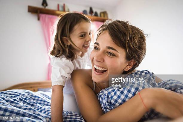 Young woman and daughter on bed in holiday chalet, Tyrol, Austria