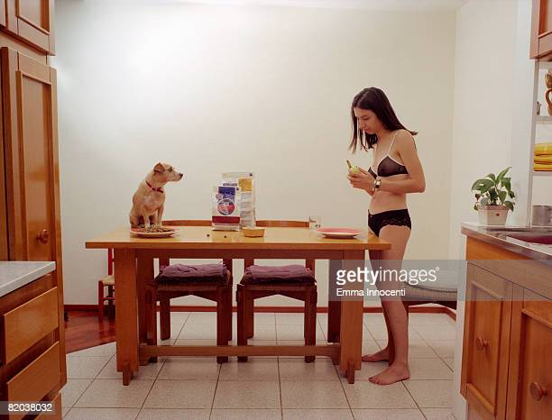 Young woman and dog in kitchen