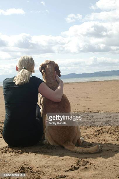 Young woman and dog sitting on beach at dawn, rear view