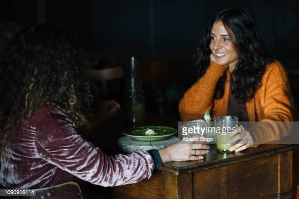 young woman and female friend sharing a meal at table - low key - fotografias e filmes do acervo